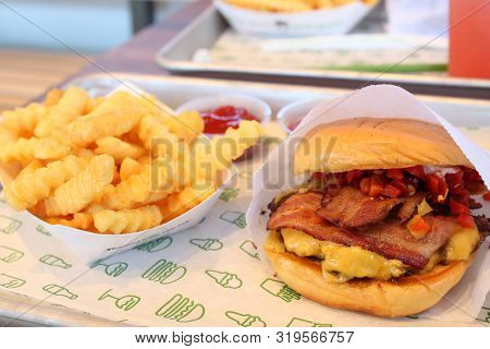 Shake Shack Cheeseburger With Bacon And Cherry Peppers On A Soft Buttery Bun With Crinkle Cut Fries