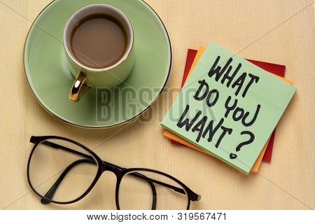 What do you want? Handwriting on a note with a cup of coffee. Personal development, aspiration and career concept.