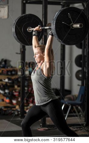 Young pretty female weight lifter lifting heavy barbell over her head.