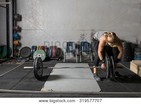 Young female power lifter loading weights onto barbell.
