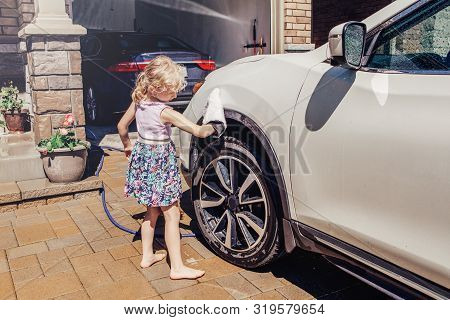 Cute Preschool Little Caucasian Girl Child Washing Cleaning Car And Wiping Glass Window On Driveway