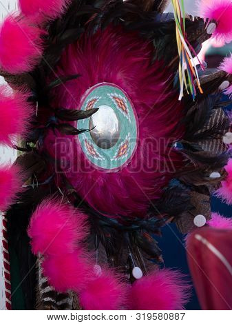 Close Up Of A Fuchsia And Black Feather Bustle With A Silver Medallion In The Center. Photographed A