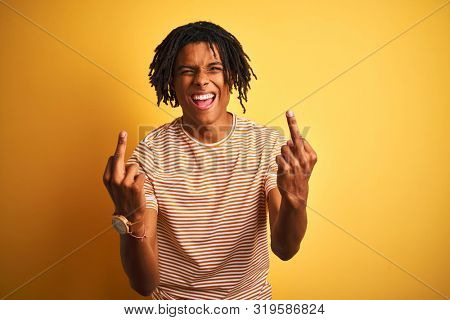 Afro man with dreadlocks wearing striped t-shirt standing over isolated yellow background Showing middle finger doing fuck you bad expression, provocation and rude attitude. Screaming excited poster