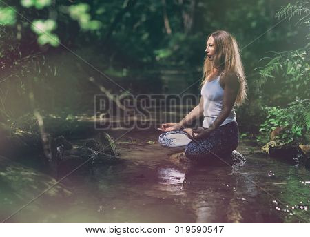 Woman in the woods sitting on the creek rock practicing yoga, wellness and wellbeing concept. Padmasana lotus pose.