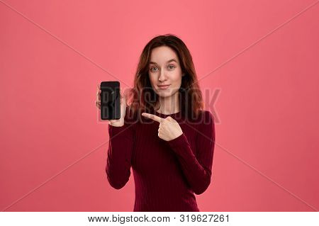 Excited Pretty Brunette Girl Pointing At The Screen Of A Mobile Phone With A Finger While Standing O