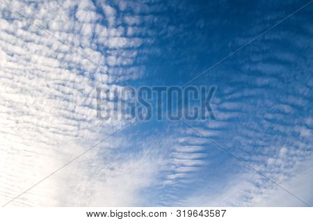 Blue dramatic sky background. Picturesque colorful clouds lit by sunlight. Vast sky landscape panoramic scene, colorful sky view, sunny evening sky background, vast blue sky scene