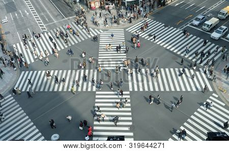 People Passing The Street Crossing In Ginza District, Tokyo. Crosswalk. Intersection In Tokyo.