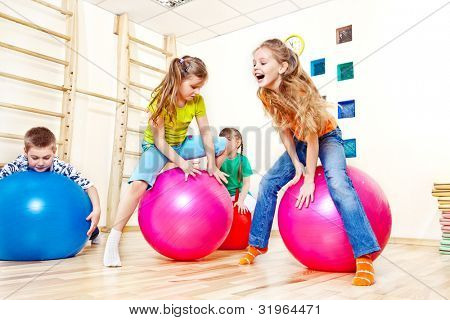 Active kids jump on gymnastic balls