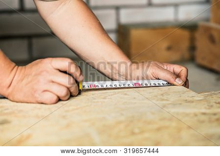 Builder Measures Osb Sheet During New Home Construction Or Renovation