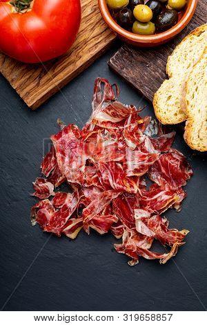 Appetizing Slices Iberian Ham In The Foreground. Olive Oil, Bread, Fresh Tomato, Olives. Black Backg
