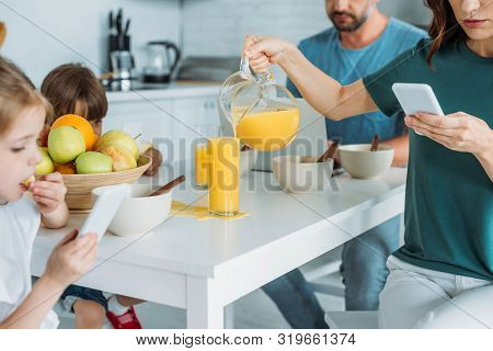Cropped View Of Woman With Smartphone Overfilling Glass With Orange Juice While Sitting At Kitchen T