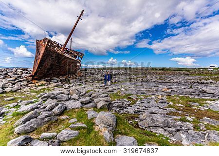 Couple Of Tourists Next To The Plassey Shipwreck On The Stunning Rocky Beach Of Inis Oirr Island, Ab