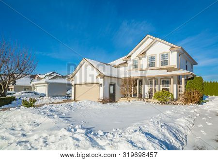 Family House With Driveway And Front Yard In Snow On Winter Sunny Day. Luxury Residential House With