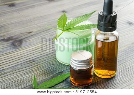 Cannabis CBD oils in glass bottle and CBD lotion gel little jars with hemp leafs on wooden table