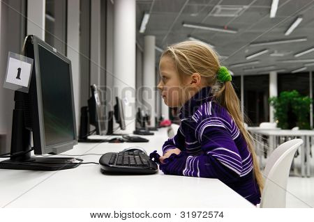 Little Girl Use Computer In A Library