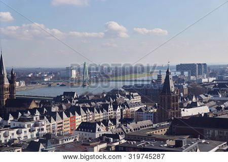 poster of Panoramic aerial view over Cologne historic city center, downtown, with colorful historical buildings, gothic cathedral towers, the Rhine river and modern bridge against beautiful sunny spring sky.
