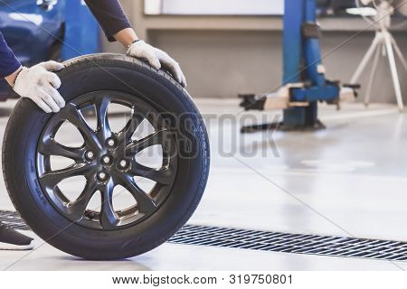 Asian Man Mechanic Inspection Service Maintenance Car Holding Tyre Or Tire Car Inspection For Measur