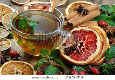 Cup Of Mint Tea On A Wooden Table. Dried Citrus Fruits, Mint Leaves, Rose Hips And Brewed Mint. Alte