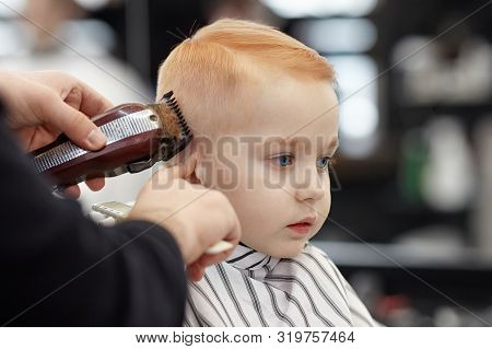 Cute Ginger Baby Boy With Blue Eyes In A Barber Shop Having Haircut By Hairdresser. Hands Of Stylist