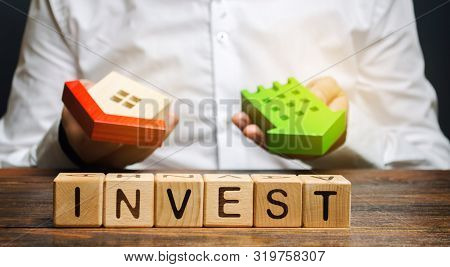 poster of Wooden blocks with the word Invest and houses in the hands of a businessman. The concept of investing in real estate construction. Effective investment. Buying apartments. Business and finance