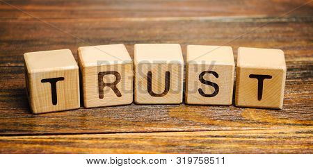 Wooden Blocks With The Word Trust. Trust Relationships Between Business Partners, Friends, Relatives