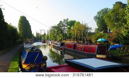 Narrowboats Moored By Tow Path On Grand Union Canal At Stoke Bruerne, England