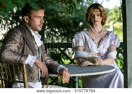 Handsome Young Couple In Vintage Clothing Sit In Gazebo Deep In Thought.