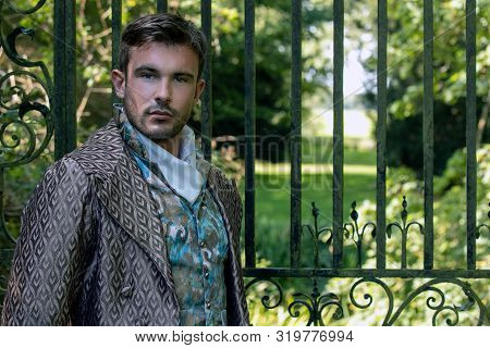 Portrait Of Attractive Gentleman Dressed In Vintage Costume Standing In Stately Home Courtyard With