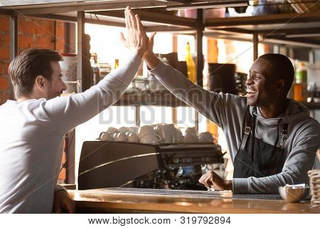 Happy African Barista Giving High Five To Customer In Coffeeshop