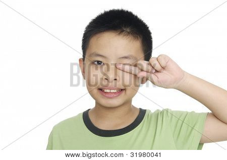 A tired little boy rubbing eyes, isolated on white