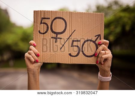 Gender Equality Concept As Woman Hands Holding A Paper Sheet With Male And Female Symbol Over A Crow