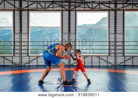 A Little Wrestler Boy In A Sports Tights Wrestles With An Adult Male Wrestler On A Wrestling Carpet