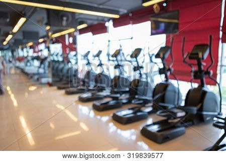 Abstract Blur Of Defocused Sport Gym Interior And Fitness Health Club With Sports Exercise Equipment