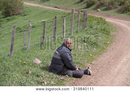 Rasht, Gilan, Iran 05 05 2019. A Tired Rural Man Sitting Next To The Road On The Floor, A Farm Is En