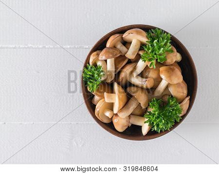 A Bowl Of Wild Mushrooms And Parsley Leaves On A White Wooden Table. The View From The Top. Natural