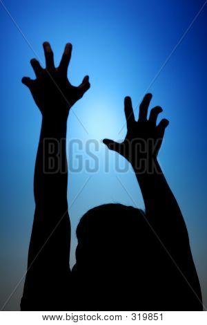 Silhouette Of Man Reach Towards The Sky