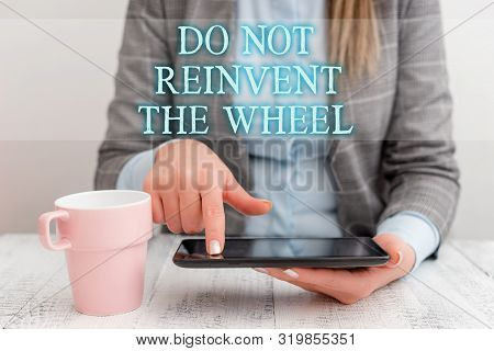 Handwriting text writing Do Not Reinvent The Wheel. Concept meaning stop duplicating a basic method previously done Business woman sitting with mobile phone and cup of coffee on the table. poster