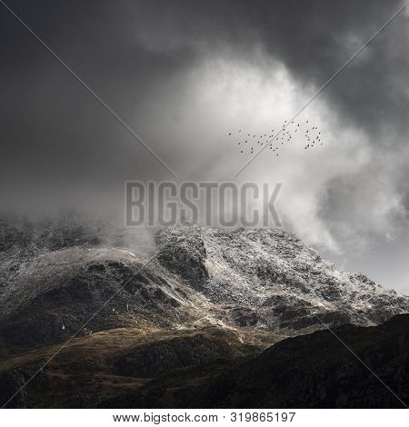 Stunning Moody Dramatic Winter Landscape Image Of Snowcapped Tryfan Mountain In Snowdonia During Sto