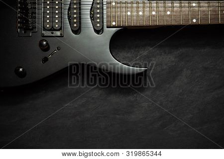 Black Electric Guitar On Black Cement Floor. Top View And Copy Space For Text. Concept Of Rock Music