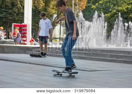 Kharkiv, Ukraine, August, 2019 Teenagers With Skateboards In City Landscape. Modern Active Lifestyle