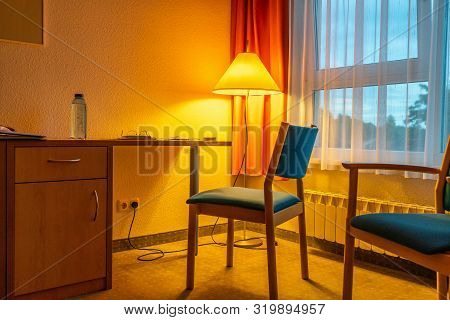 A Room Filled With Golden Light  From Yellow Floor Lamp With Two Blue Chairs And A Window With Orang
