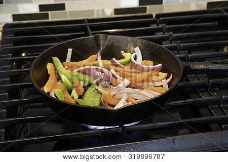 Sliced Green And Red Bell Peppers And Onions Grilling In A Cast Iron Pan