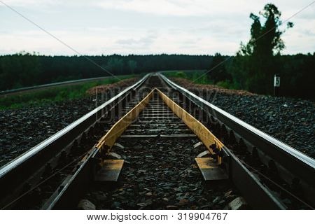 Dramatic Scenery With Railway In Perspective And Turn. Journey On Rail Track. Sleepers And Rails Clo