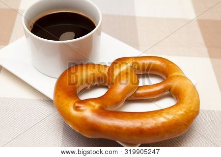 German Style Pretzel With A Cup Of Coffee A Snack Of A German Style Pretzel With A Cup Of Coffee