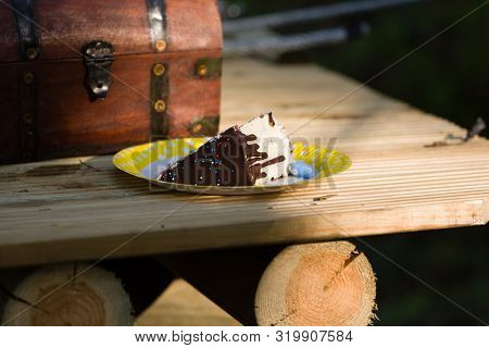 A Slice Of Cake With Chocolate Topping And Colorful Sugar On Wooden Boards With And Old Fashioned Ir