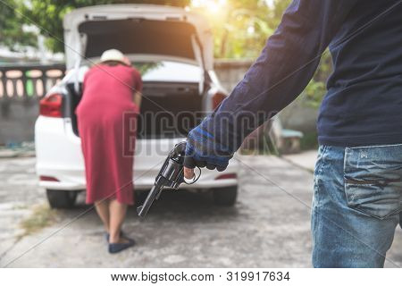 Thief With Gun Trying To Steal Car Or Money From Unaware Woman With Automobile (theft Concept)