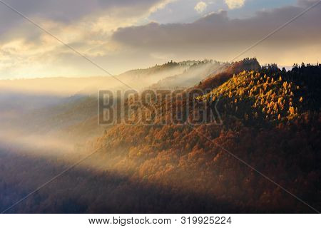 Autumnal Mountain Landscape At Foggy Sunrise. Beautiful Nature Scenery. Cloudy Weather, Forests In F