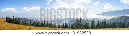 Mountain Panorama With Forest On Meadow. Beautiful Autumn Weather. Clouds And Fog Rising Above The H