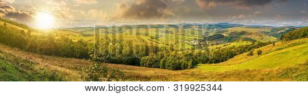 Beautiful Countryside Panorama In Autumn At Sunset. Grassy Hills And Meadows. Trees With Green Folia