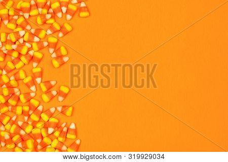 Halloween Candy Corn Side Border. Top View Against An Orange Background With Copy Space.